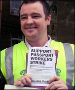 PCS passport workers on strike in Belfast, holding up Socialist Party leaflet, photo by Peter Hadden