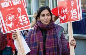Kshama Sawant, Socialist Seattle councillor, giving out placards at a protest for $15 an hour, photo Socialist Alternative