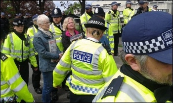 Two Socialist Party members standing their ground surrounded by police, photo Sarah Wrack