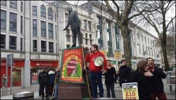 Jaime Davies speaking next to a statue of Nye Bevan