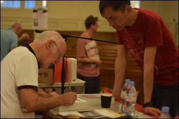 Peter Taaffe signing a copy of his new book, London launch meeting, 25.5.17, photo by Mary Finch