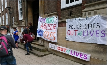 A banner outside the meeting photo COPs campaign
