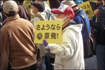 Protesters in Japan march with signs reading 'goodbye nuclear power,' photo by James Clement