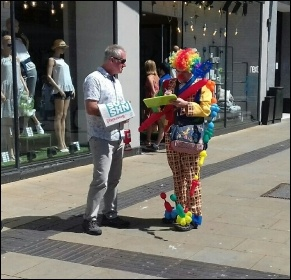 Clown signs NHS petition in Swansea, photo Alec Thraves