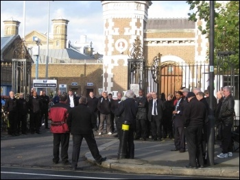 Prison officers outside Wormwood Scrubs prison listening to Socialist Party member Keith Dickinson address them using a megaphone on 30th November 2011